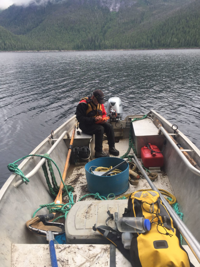 ecologist on boat with sampling equipment