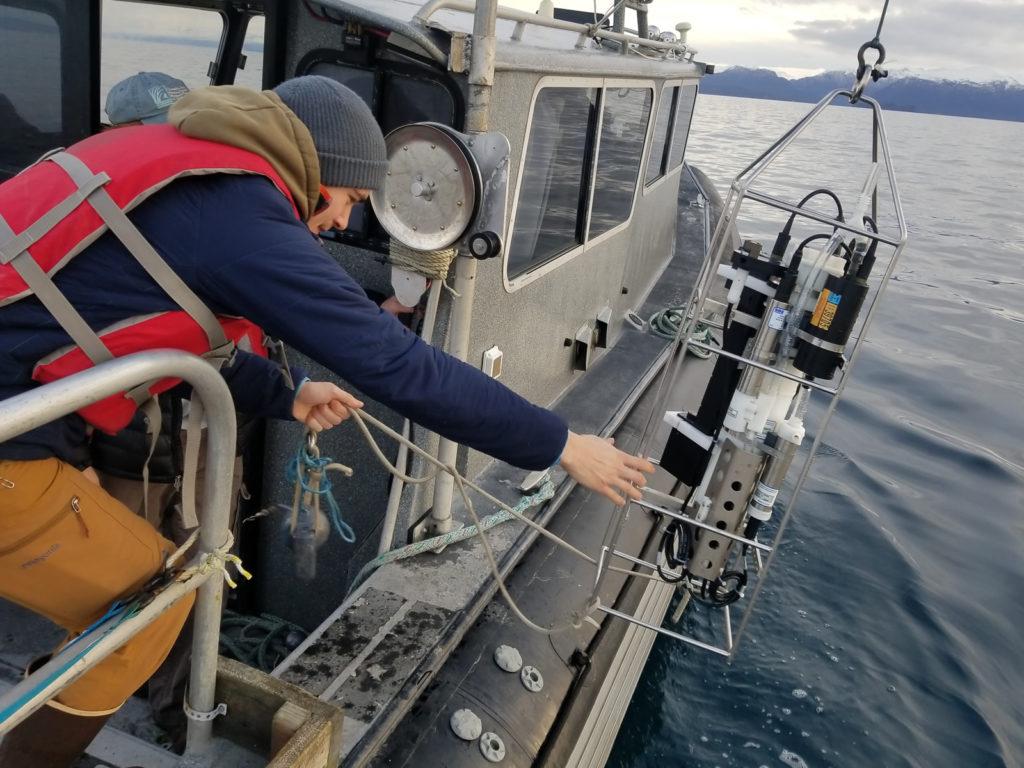 researcher deploying ocean monitoring equipment